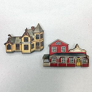 Trämagneter där man ser stationshuset och brunnen i Dals Rostock av Kerstin Ljungqvist..
