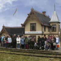 2005 års bild:  Dalslands Järnväg firar 125-årsjubileum 2004. Folk har samlats framför stationen för att åka med ångtåget den 18 september. Kompositionen av bilden är snarlik 2001 års bild.
