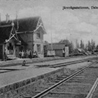 2013 års bild:  Bilden är från ett vykort från slutet av 1910-talet eller början av 1920.talet. Till höger om stationen kan man se vedboden och framför den en anslagstavla med reklamskyltar. Vedboden har samma sorts papptak och nockdekoration som stationshuset.