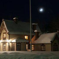 2017 års bild: Bild på stationshuset med snö och måne. Bild från snövintern 2011.