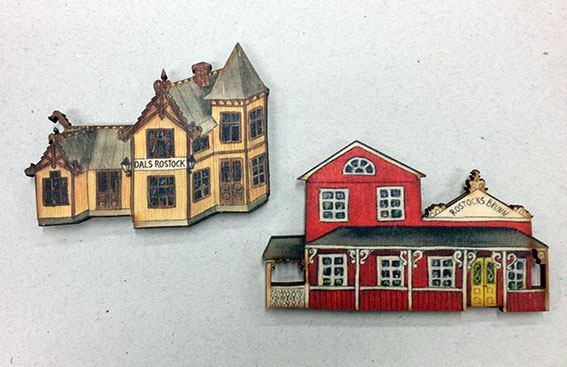 Handgjorda trämagneter där man ser stationshuset och brunnen i Dals Rostock. Skapade av Kerstin Ljungqvist.